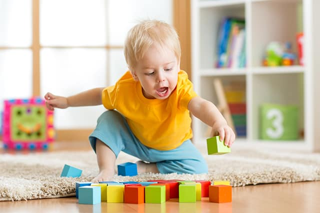a toddler playing with wood blocks